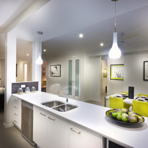 A moody and stylish image of a house with kitchen and attached living room and food placed on kitchen shelf